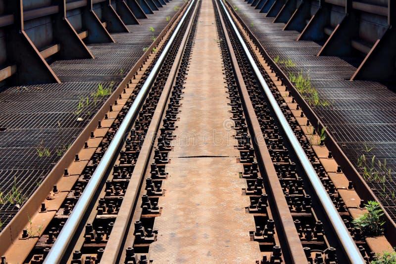 强的老生锈的金属铁路桥梁有坚硬支持和铁路轨道在中部登上了与大螺丝 库存照片