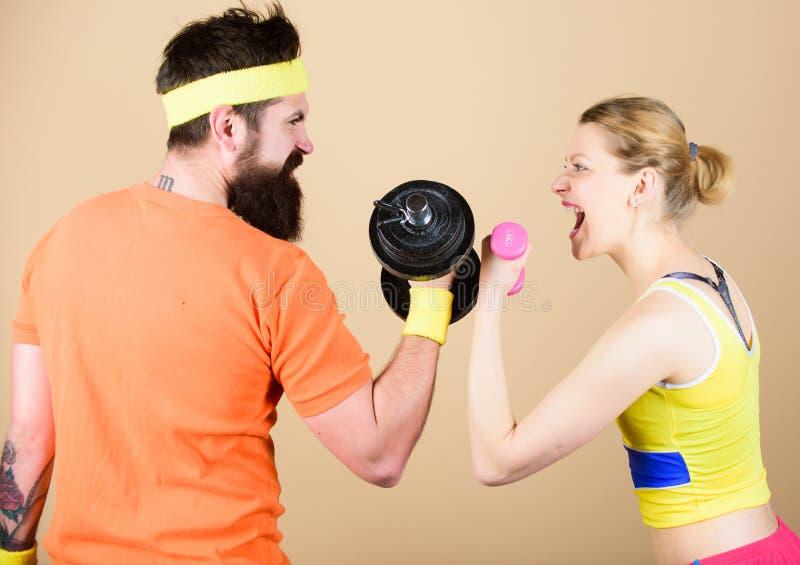 强的肌肉和力量 体育哑铃设备 在健身房的运动的夫妇训练 运动竞争 增强的人肌肉向量重量 图库摄影