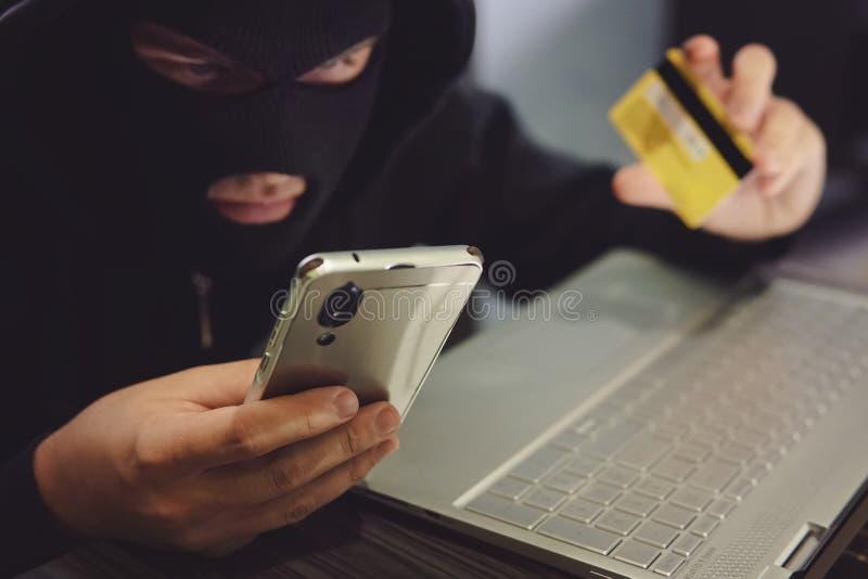 强盗面具的男性黑客在某一骗局使用电话、信用卡和膝上型计算机 网络窃贼女用披肩个人资料和 免版税图库摄影