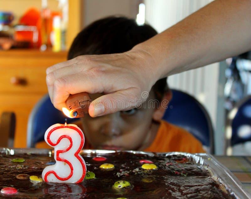 当一个小孩观看它时,递点燃一个生日蜡烛 库存照片