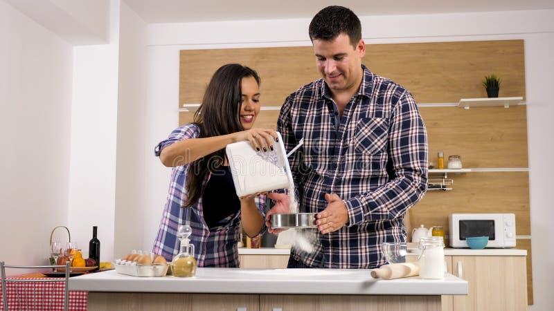 当他为她时,烹调美丽的妻子帮助她的丈夫 库存照片
