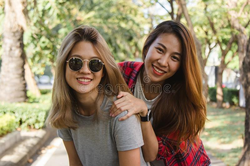 当他们做城市旅行时,愉快的年轻亚裔妇女结合互相使用 免版税图库摄影
