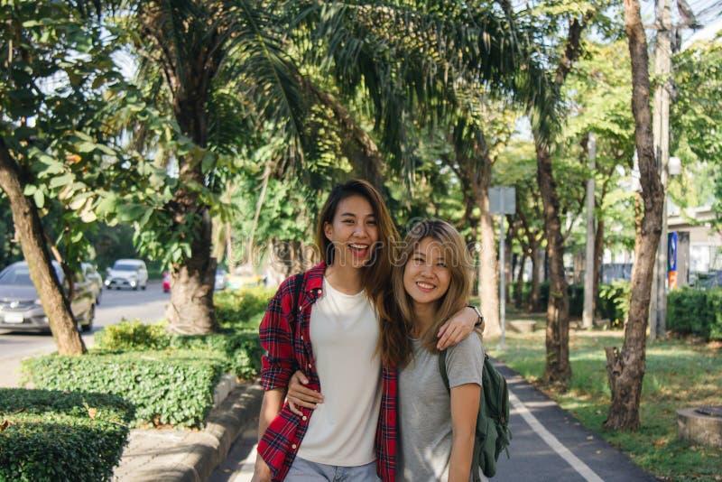 当他们做城市旅行时,愉快的年轻亚裔妇女结合互相使用 免版税库存图片