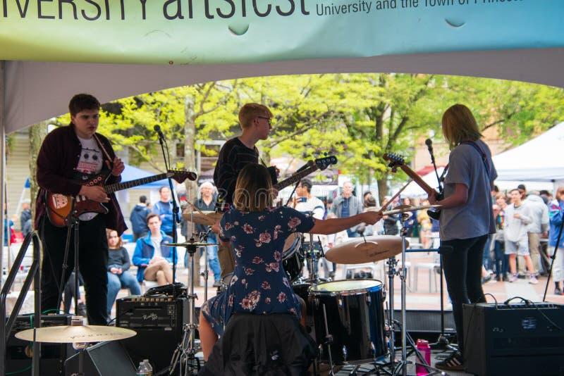 当他们弹奏他们的在人群前面的仪器在一个室外市场,乐团从后面看 有妇女 图库摄影
