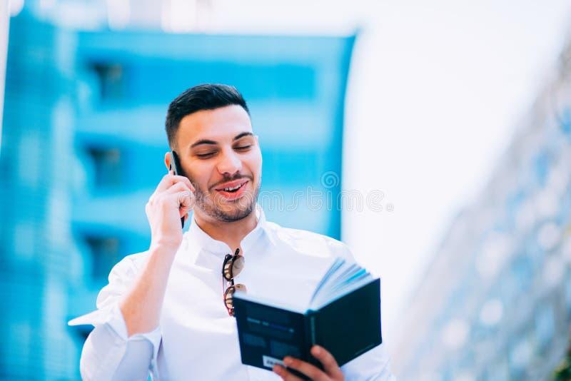 当他拿着一支笔时,在衣服的年轻商人在他附近注视着财务中心 库存照片