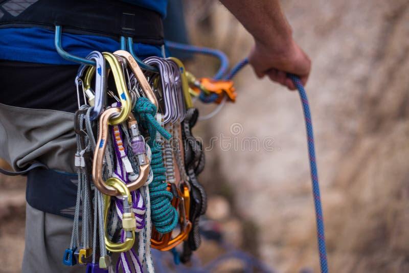 当他攀登岩石墙壁时,攀岩运动员系住他的伙伴 库存图片