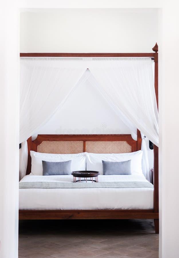 当代殖民地白色有四根帐杆的卧床床 免版税库存图片