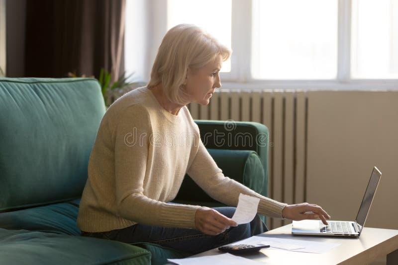 当代老妇人通过笔记本电脑在线支付账单 库存图片