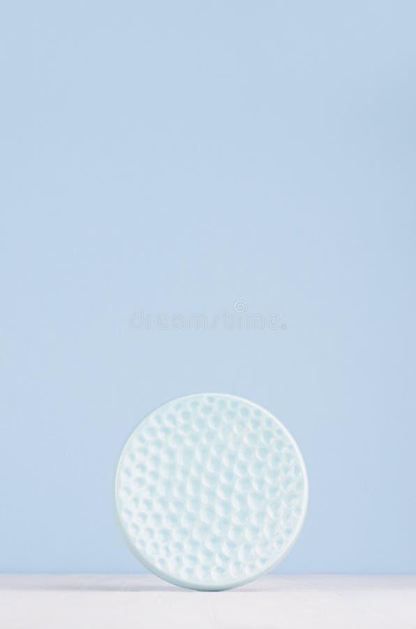当代艺术摘要背景,内部-在软的淡色蓝色颜色的装饰陶瓷光滑的有肋骨球形在白色木头 图库摄影