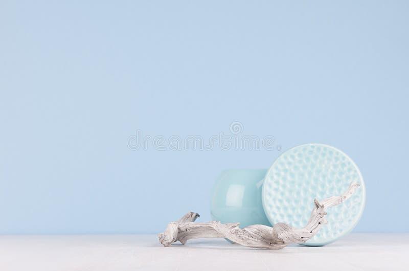 当代艺术-抽象内部-装饰陶瓷光滑的有肋骨碗、球形花瓶和干破旧的枝杈在蓝色 免版税库存图片