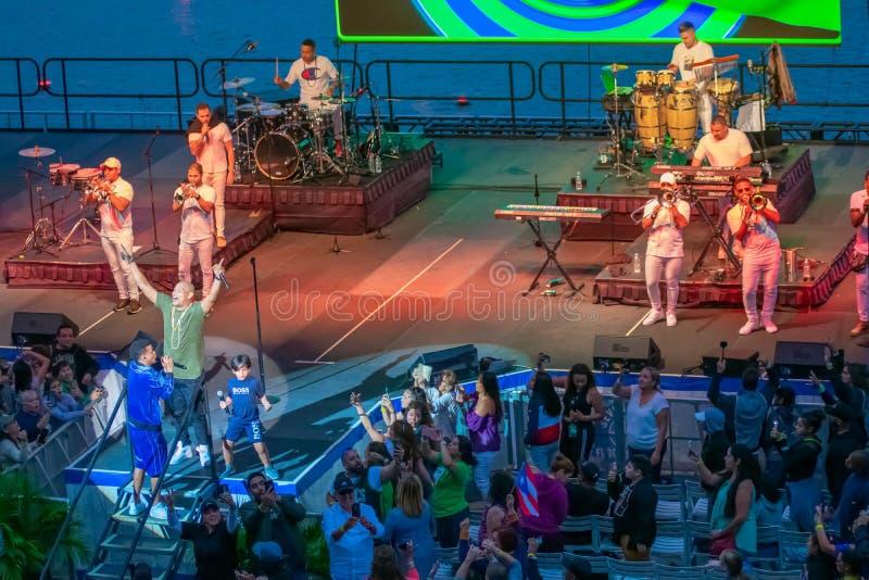 当兰迪马尔科姆由真特de佐娜唱歌在国际驱动的A时,Seaworld亚历山大德尔加多举他的手对观众 图库摄影
