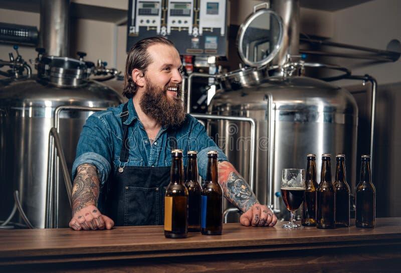 当前啤酒的一个人在microbrewery 免版税图库摄影