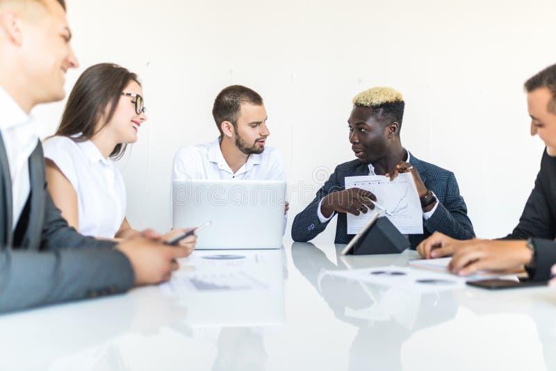 当前图的英俊的年轻非裔美国人的商人在与队的一次会议上 小组工作 免版税图库摄影