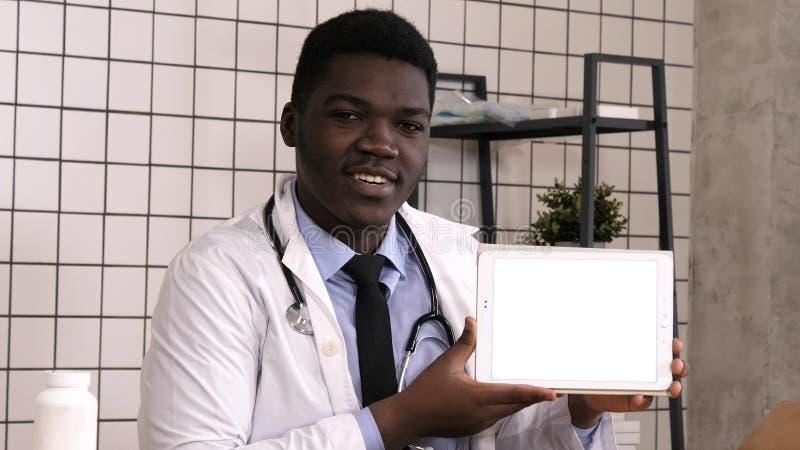 当前在片剂屏幕上的英俊的严肃的非洲医生产品 空白显示 免版税库存照片