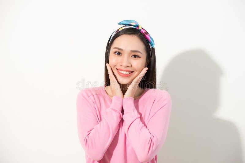 当前她的面孔用手的逗人喜爱的亚洲人接触在V字型、画象、skincare和化妆概念,桃红色衬衣的面孔,白色 库存图片
