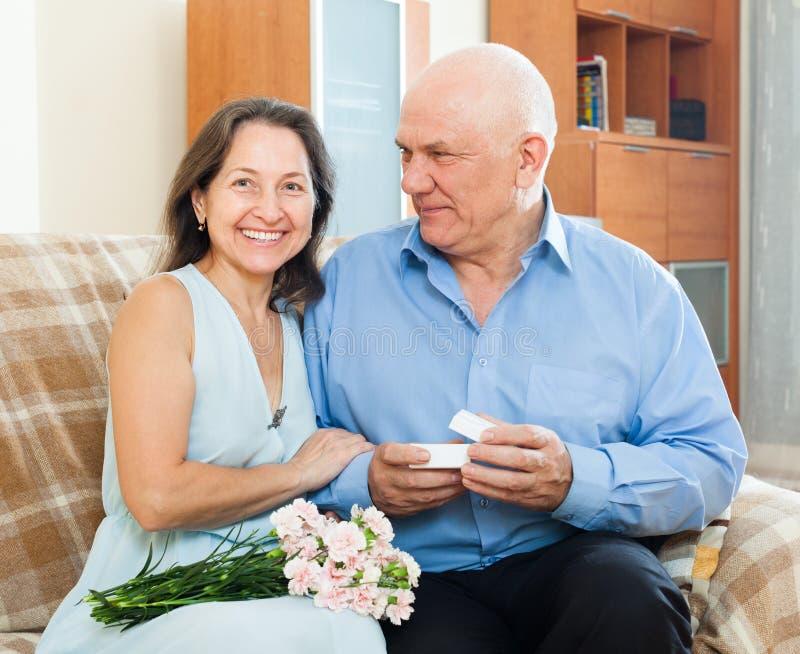 当前微笑的成熟妇女珠宝的老人 库存照片