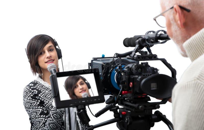 当前报告的俏丽的年轻女人新闻工作者在白色的电视演播室 免版税库存图片