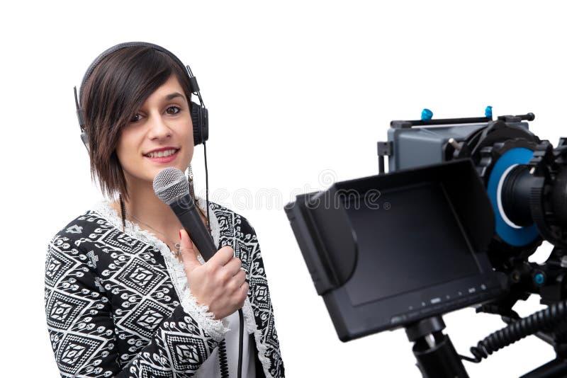 当前报告的俏丽的年轻女人新闻工作者在白色的电视演播室 库存照片