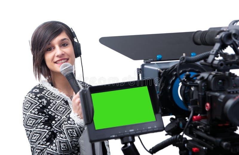 当前报告的俏丽的年轻女人新闻工作者在白色的电视演播室 库存图片