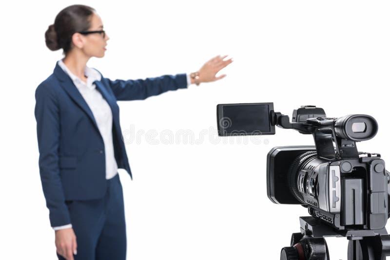 当前某事在照相机前面的美丽的女性新闻广播员, 免版税图库摄影