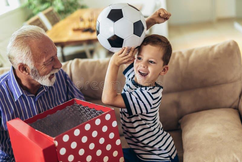 当前礼物的资深祖父对愉快的孙子 图库摄影