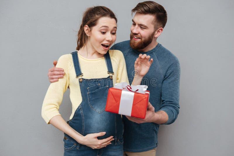 给当前箱子的愉快的快乐的丈夫他怀孕的妻子 库存照片