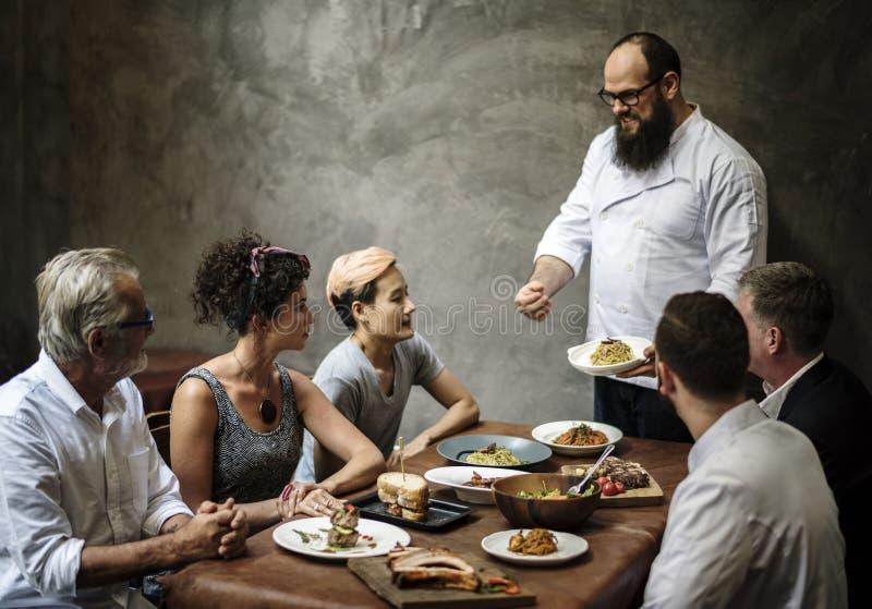 当前食物的厨师对顾客在餐馆 图库摄影