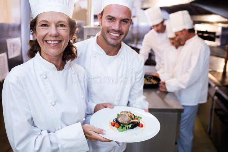 当前他们的盘的两位厨师 免版税库存照片