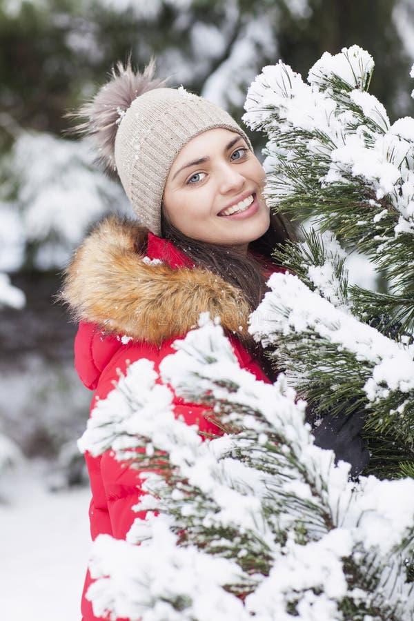 当在公园时,下着雪美丽的妇女是愉快的 库存照片