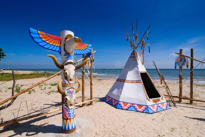 当地美洲印第安人圆锥形帐蓬和标识杆在海滩蓝色sk 库存照片