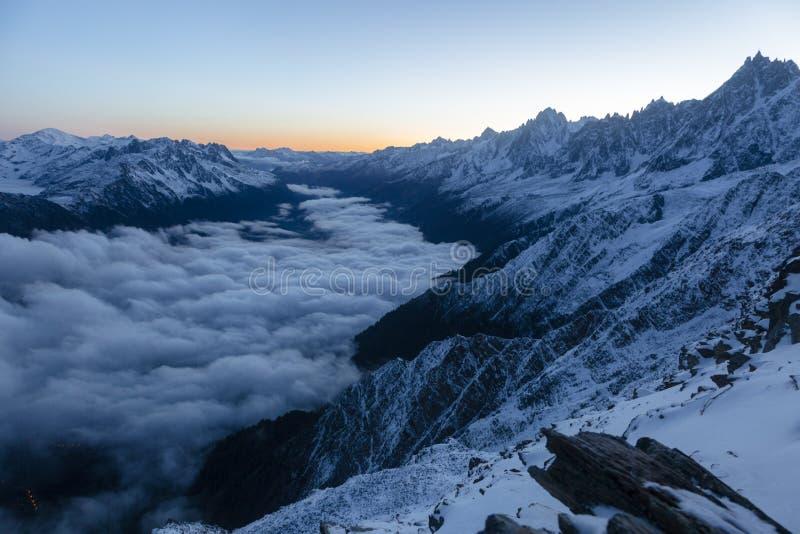 当太阳在法国阿尔卑斯,升起美好的锋利的峰顶开始发光 免版税库存图片