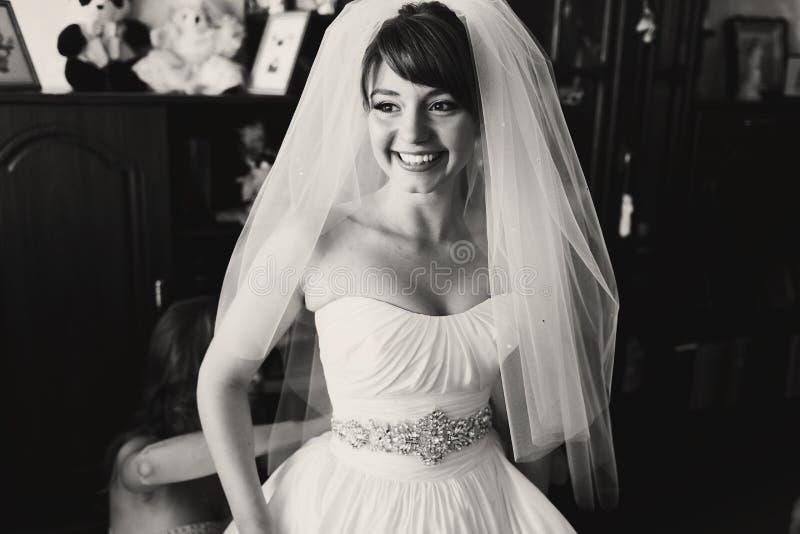 当女傧相按她的礼服时,新娘恳切地微笑 免版税库存照片