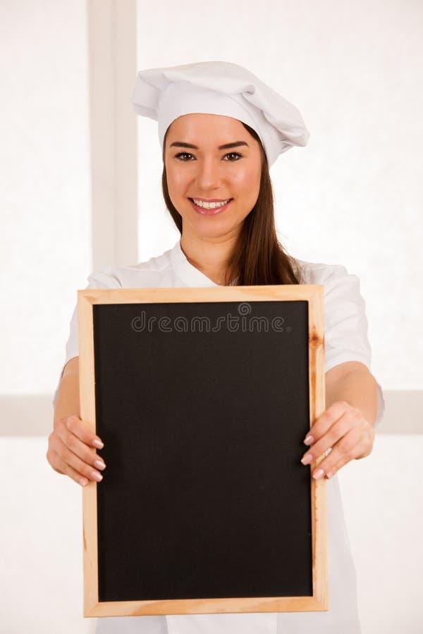 当她准备咕咕叫,年轻白肤金发的厨师woamn拿着厨具 库存图片