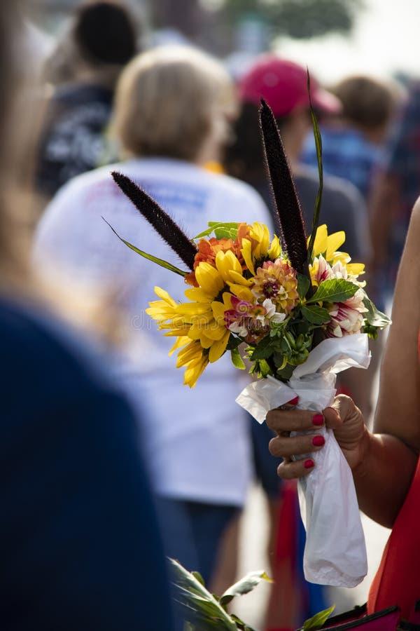 当她拿着花boquet与在塑料包裹的词根的作为peop,被弄脏的无法认出的人群黑人妇女武装并且递 库存照片