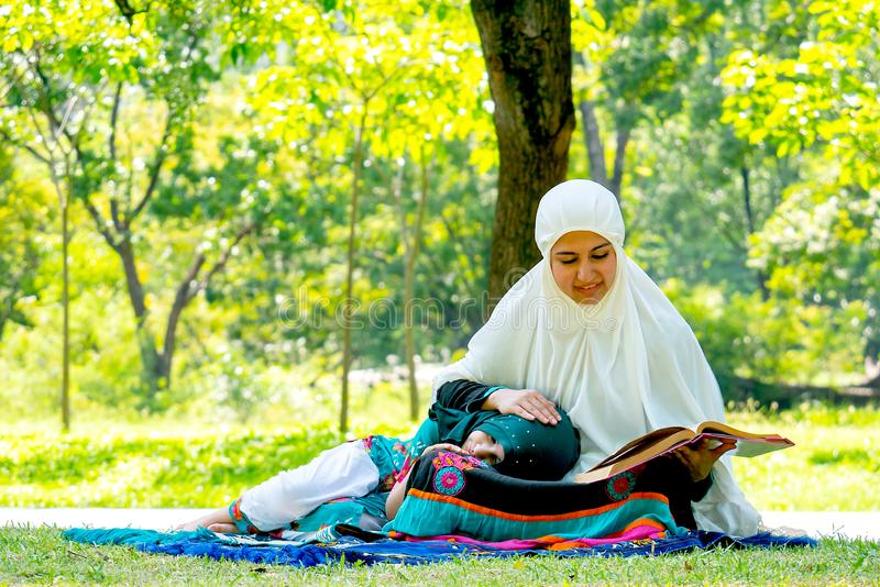 当她的女儿放下对她的膝部时,回教母亲读了宗教课本 在白天,他们在绿色庭院里停留 免版税库存图片