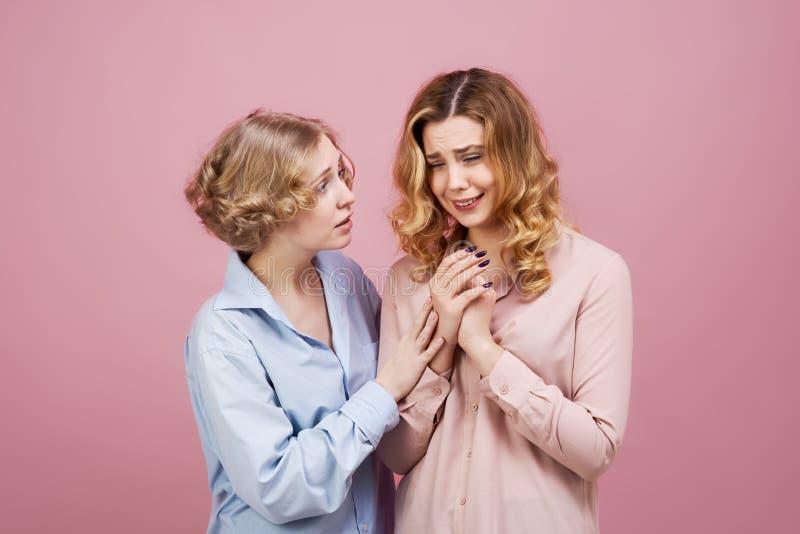 当她的朋友握她的手并且设法使她镇静下来时,一名年轻美丽的妇女啜泣 坏消息的概念,分开 免版税库存照片