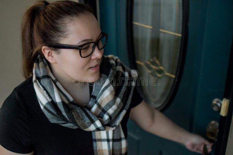 当她离开在家与一个行李袋一条胳膊,妇女锁她的前门 库存图片