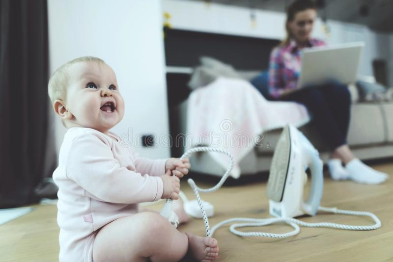 当妇女在膝上型计算机坐长沙发时,与危险导线的小儿童游戏 免版税库存照片