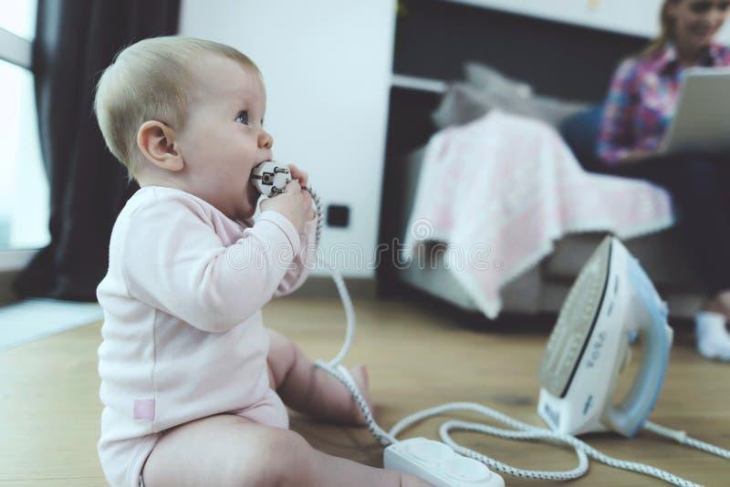 当妇女在膝上型计算机坐长沙发时,与危险导线的小儿童游戏 库存照片