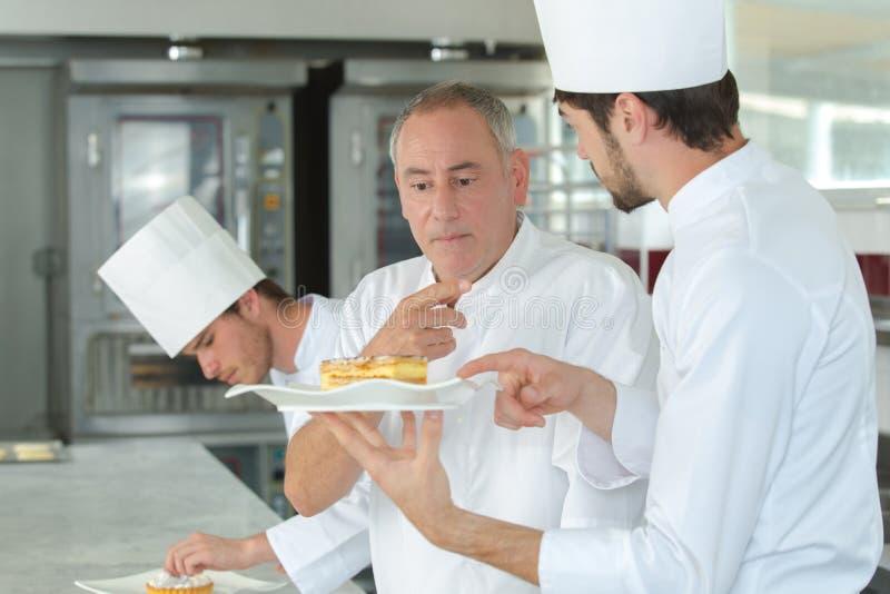 当学徒厨师在与老练的大师一起使用 库存照片