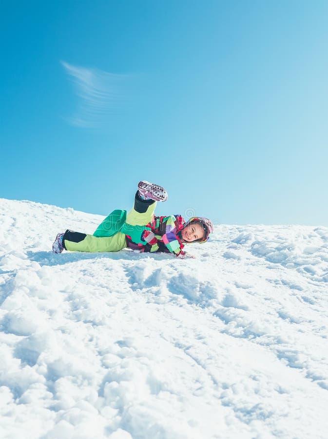 当幻灯片从雪小山时,击倒女孩获得乐趣 她是机会 免版税图库摄影
