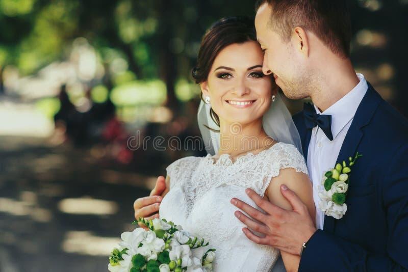 当新郎拿着她的肩膀招标时,新娘微笑 图库摄影