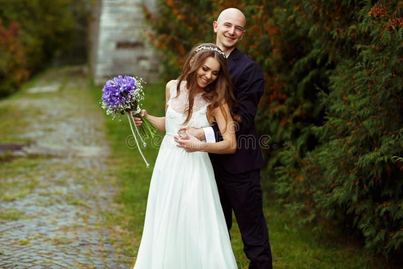 当新郎从后面时,体贴拥抱她新娘微笑 免版税库存照片