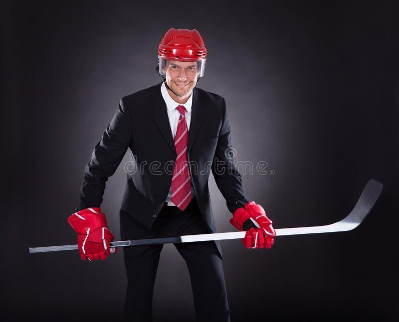 当曲棍球运动员穿戴的商人 库存图片