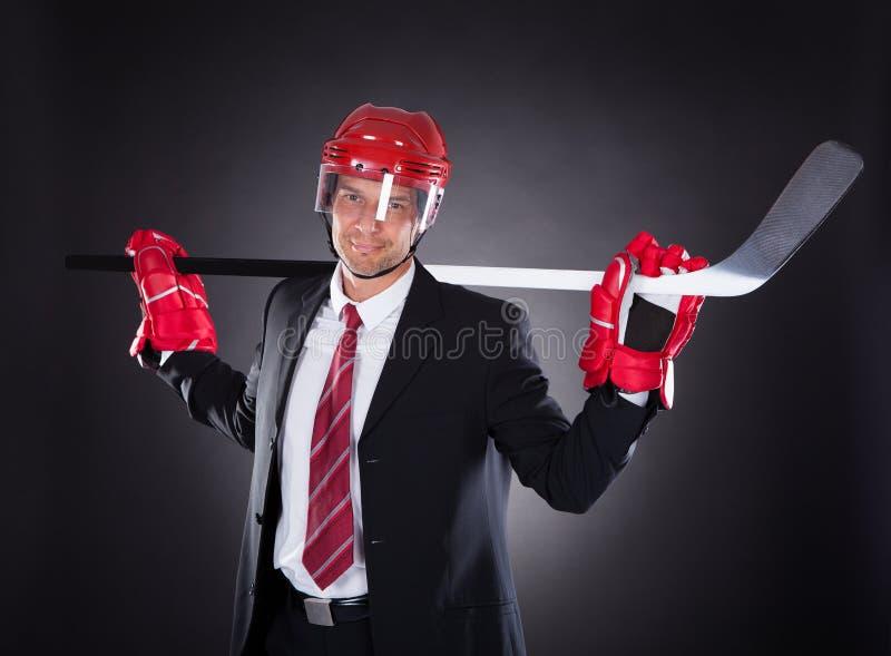 当曲棍球运动员穿戴的商人 免版税库存照片