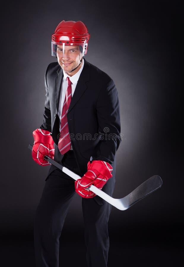 当曲棍球运动员穿戴的商人 免版税库存图片