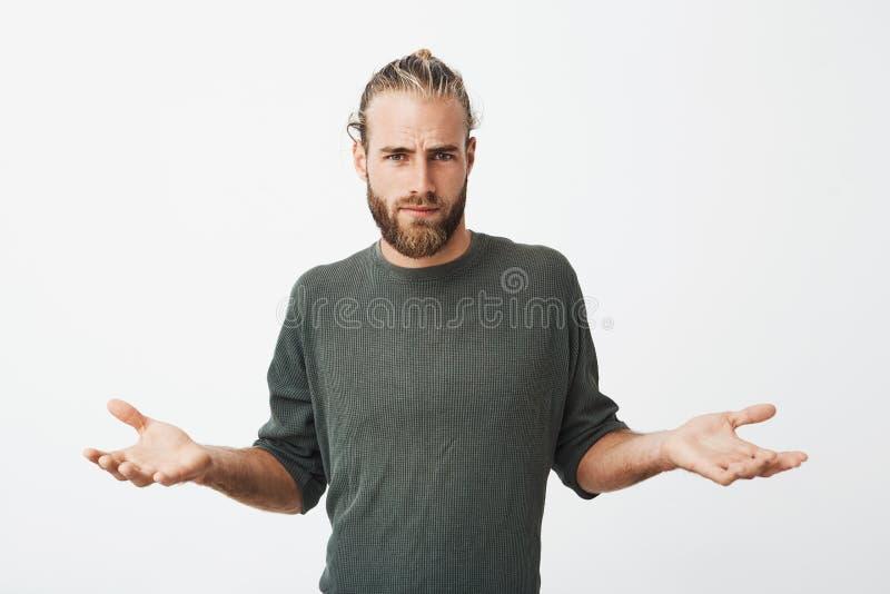 当某人推挤了,有胡子和时髦的发型的英俊的北欧人涂有玩事不恭和卑鄙表示的手 免版税库存照片