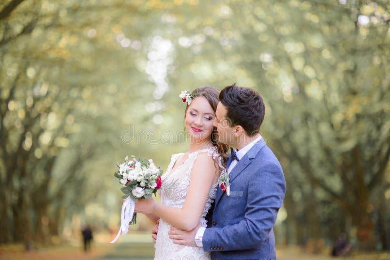 当深色的新郎握她的精美腰部时,好新娘微笑 免版税图库摄影