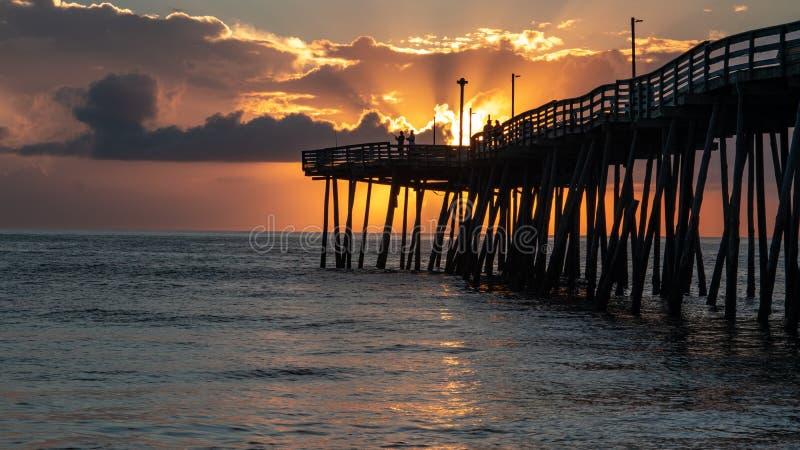 当渔夫熔铸他们的从一个老木码头的末端的线在日出,剧烈的天窗与黄光的云彩 免版税库存照片