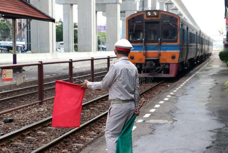 当火车登陆在平台时,火车官员行动发信号乘客和人的安全预防措施 免版税库存照片